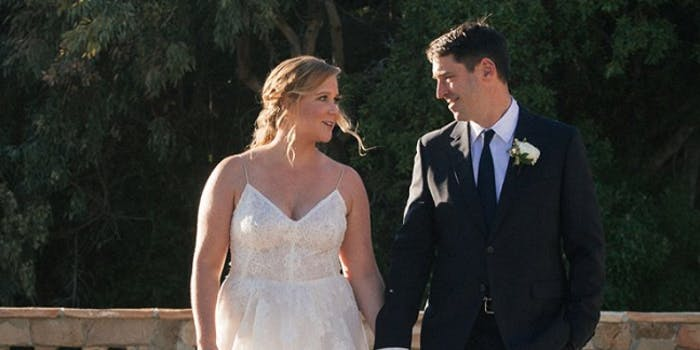 Amy Schumer and her new husband smile at each other while holding hands