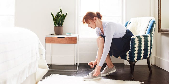 Amazon Echo dot in a bedroom while woman ties her shoes