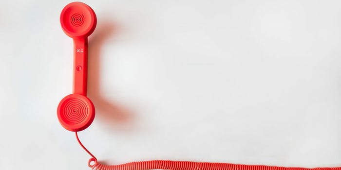 Red phone with cord on white background
