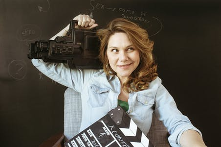 Erika Lust holds a camera and a clapperboard.