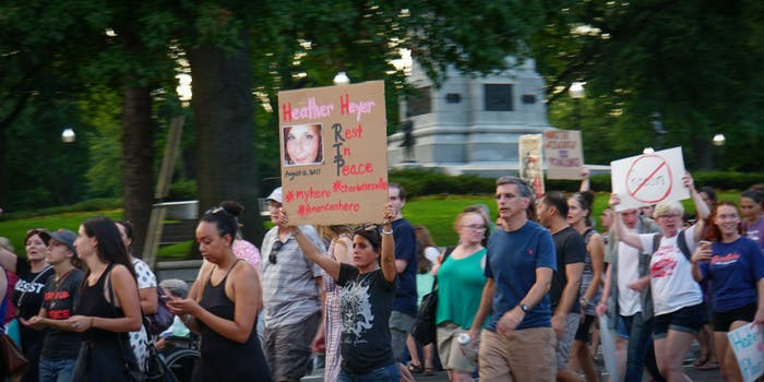 """A Charlottesville solidarity vigil held in Washington, D.C., with a woman holding up a poster featuring Heather Heyer that says """"rest in peace."""""""