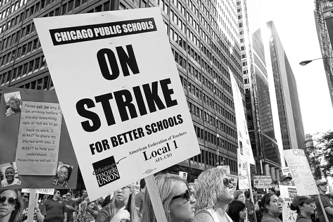 Teachers holding picket signs on strike