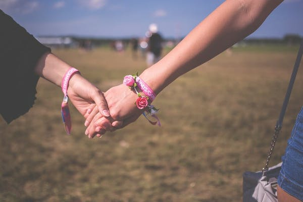 Two women hold hands in this image.