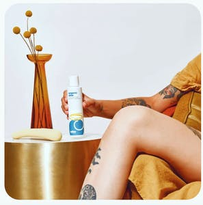 A tattooed woman holds Cake's Organic Aloe lube in her hand with a vibrator and plant on the end table next to her.