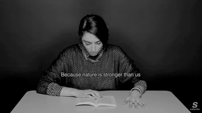 Image of a woman reading from a book with her hand gripped on the table.