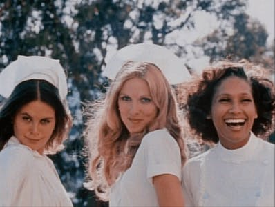 Three nurses stand smiling in uniform in a scene from night call nurse