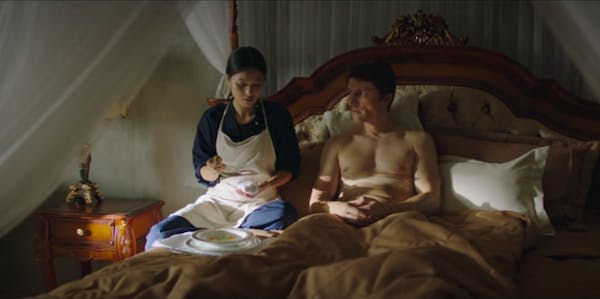 A scene from the housemaid showing a woman in an apron sitting on a bed next to a topless man