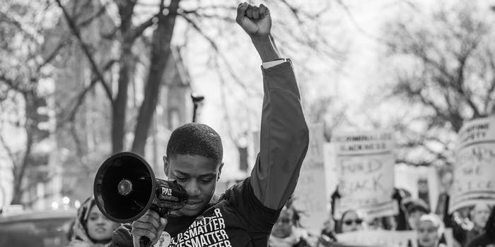 "Man in ""Black Lives Matter"" shirt raising fist, speaking through megaphone"