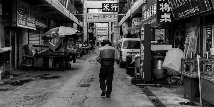 Man walking down street or alleyway.