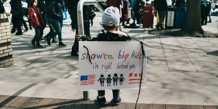 """Child with """"show 'em big kids, i'm right behind you"""" sign at March For Our Lives"""