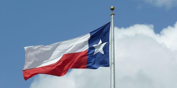 The Texas flag on a pole in a cloudy sky.