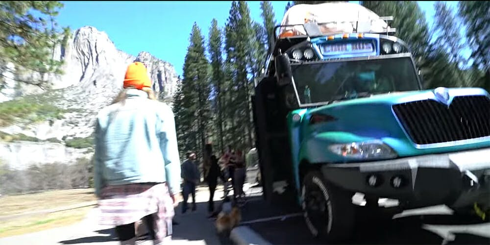 A screenshot from a Logan Paul vlog shows a tent strapped to his converted school bus in Yosemite National Park.