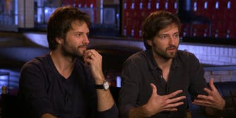 The Duffer brothers sit side by side in black shirts