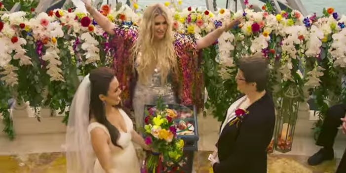 Kesha throws her hands up while officiating a wedding for two brides
