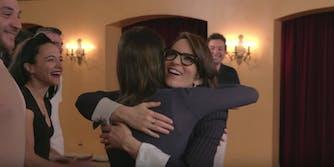 Tina Fey hugs a fan while smiling