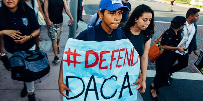 Protesters defending the Deferred Action for Childhood Arrivals (DACA) program with a poster stating 'Defend DACA.'