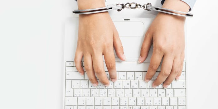 internet censorship typing on computer while handcuffed