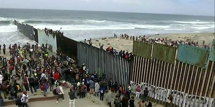 A caravan of Central American migrants standing along and sitting on the U.S.-Mexico border wall in San Diego.