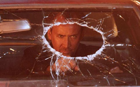 a scene from drive angry showing Nicholas Cage driving with a hole in his windscreen