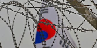 south korean flag behind barbed wire
