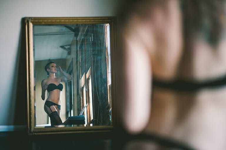 A queer model stares at themselves in the mirror in this image.