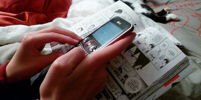 phone and hands on top of comic book