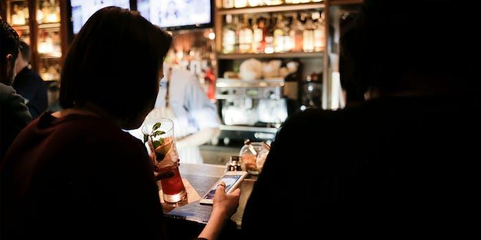 woman at bar using phone