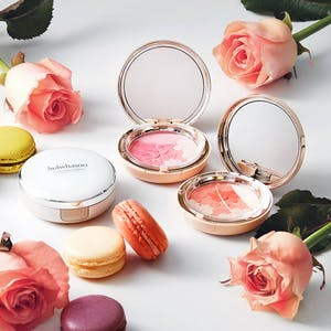Beautiful Korean beauty brand Sulwhasoo compacts surrounded by roses and macarons