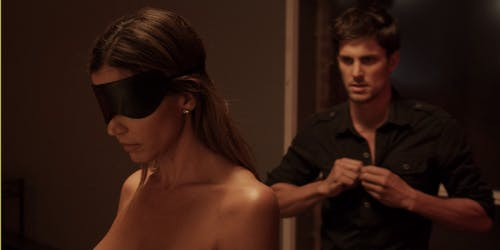 A man unbuttons his shirt as a naked woman stands blindfolded in this Amazon Prime porn scene