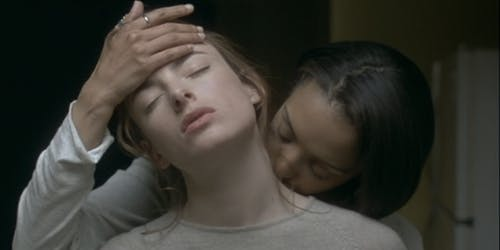 A woman kisses the neck of another woman in a scene from When Night is Falling