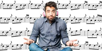 man with headphones shrugging in front of sheet music