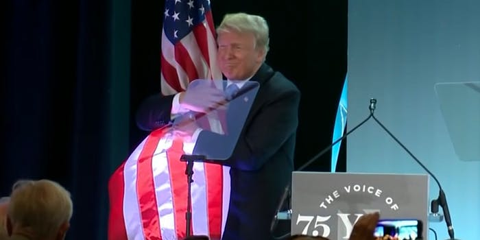 Trump hugs American flag