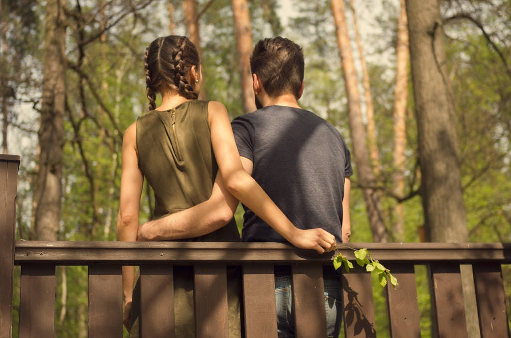 How to DTR - a photo of two people leaning casually up against a deck railing, their backs facing the camera, their arms lightly embracing each other around their waists, both facing a wooded area. The person on the left is in a green sleeveless dress and wearing braids, the person on the right has short-cropped hair and is wearing a dark navy t-shirt and jeans.
