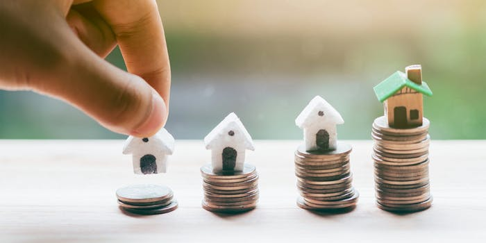 hand placing house model on stack of coins