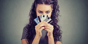 How to Protect Yourself From Online Identity Theft on the Dark Web: woman hiding face behind credit cards