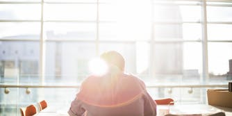 Man working at a table with lens flare