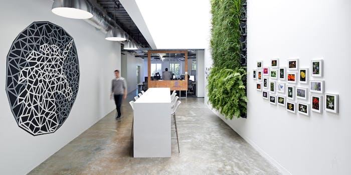 Inside Facebook HQ, man walking next to living wall