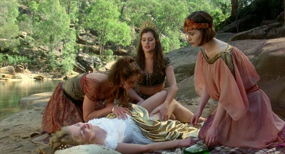 Three woman in flowing dresses caress a woman lying on the ground in a scene from Sirens