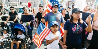 A family protesting the end of DACA, holding American flags.