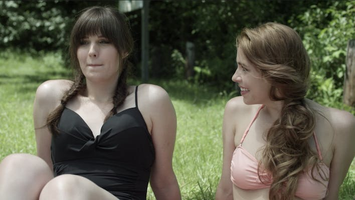 Two women in swimsuits talk in a scene from the hulu show Shame