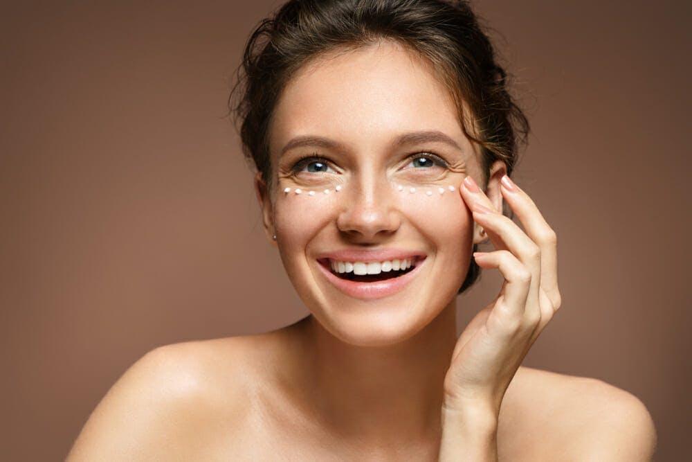 Woman putting on eye cream