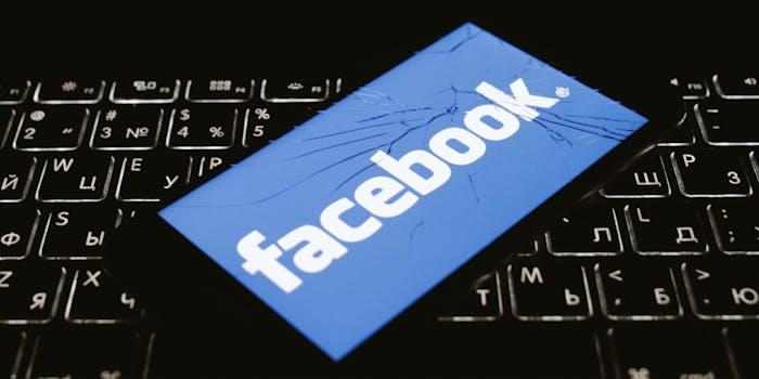 facebook logo on broken phone, sitting on top of cyrillic keyboard