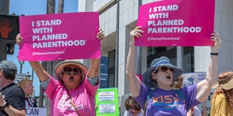 """women hold """"i stand with planned parenthood"""" signs at protest"""