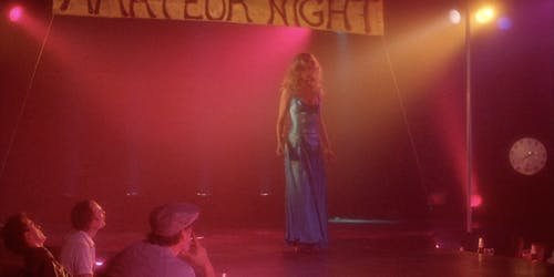 A woman stands on a stage in the movie Stripped to Kill