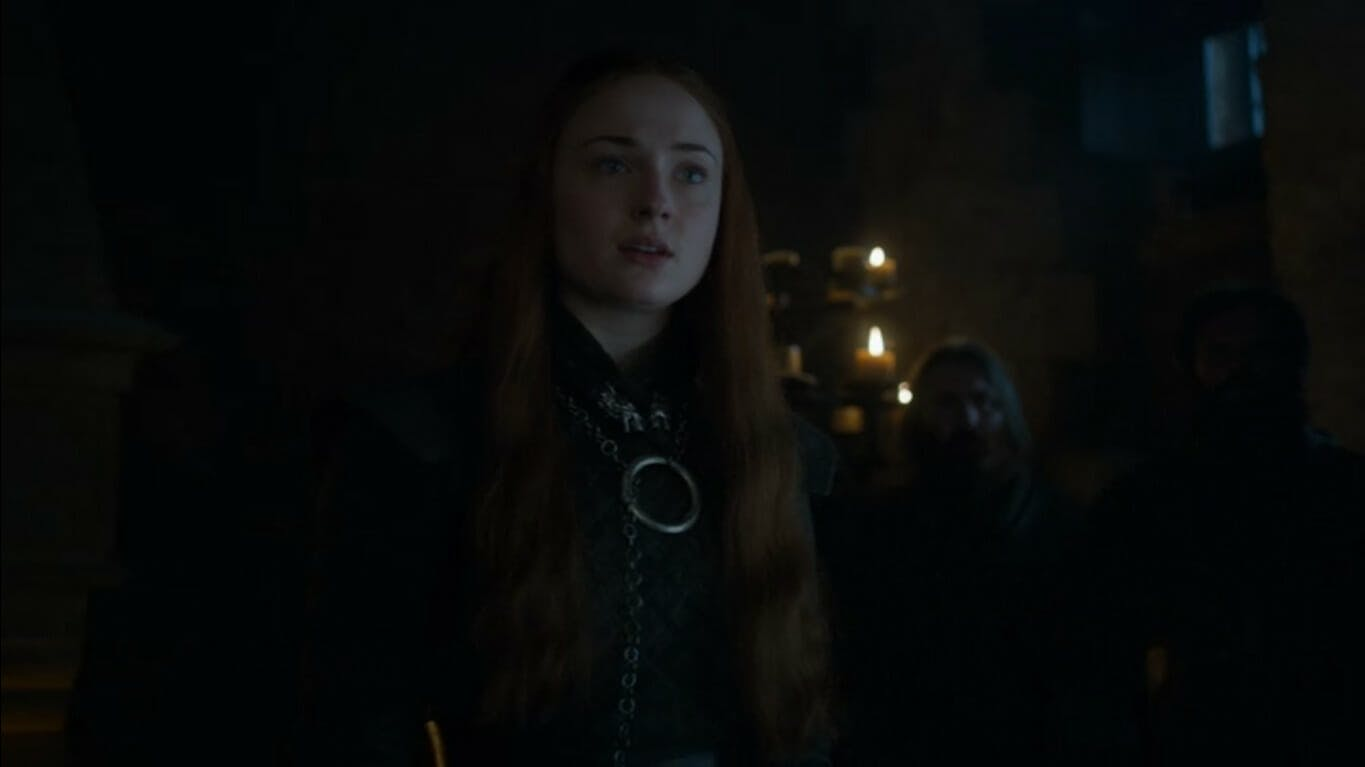 Image showing Sansa Stark standing in the dark with candles in the background