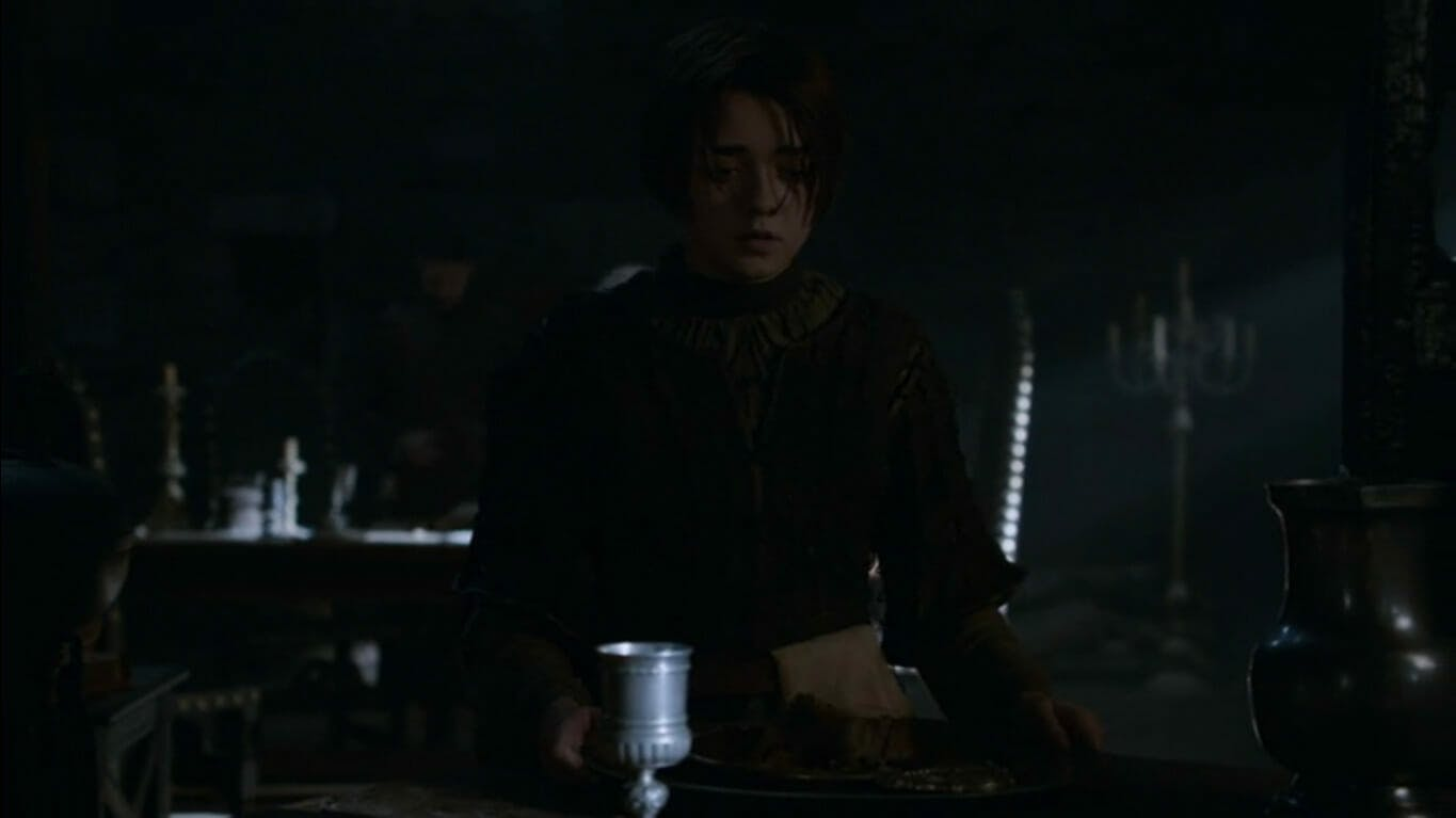 Image of Arya Stark sitting at a table in the dark