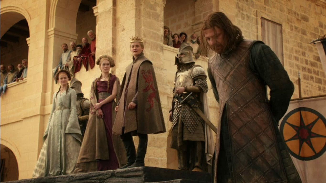 Image showing Eddard Stark with his hands tied behind his back, as Joffrey stands behind him