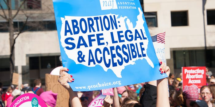 """woman holding """"abortion: safe, legal & accessible"""" protest sign"""