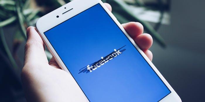 A strikethrough on a Facebook logo on a phone screen