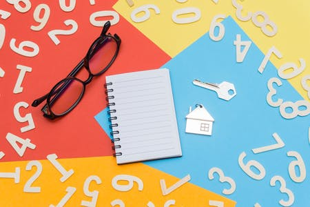 Number cut outs, a pen, pad, eye glasses, a house key, and house-shaped keychain lay on a background of multi-colored construction paper.